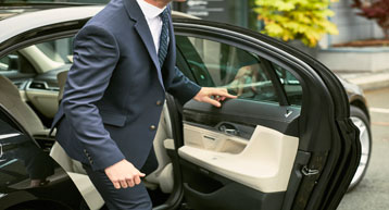 Businessman getting out of chauffeur car